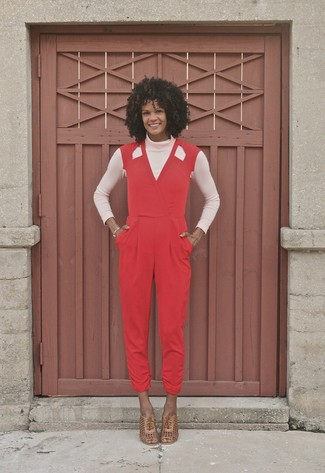 How to Wear a Jumpsuit After 40: For a totaly stylish look without the need to sacrifice on practicality, we turn to this pairing of a pink turtleneck and a jumpsuit. And if you need to easily up this look with footwear, add tan leather heeled sandals to the equation.
