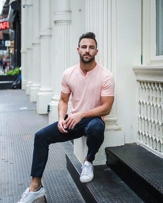 If you feel more confident wearing something comfortable, you'll love this stylish pairing of a pink v-neck t-shirt and navy chinos. This getup is complemented perfectly with white leather low top sneakers. We can't get enough of this ensemble for hot days.