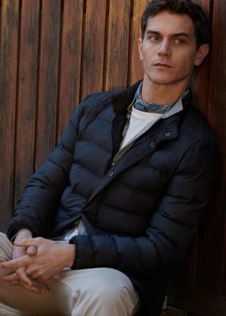 Cómo combinar: plumífero negro, cárdigan gris, camiseta con cuello circular blanca, vaqueros en beige