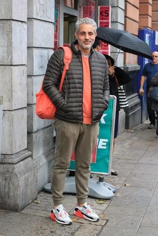 Cómo combinar: plumífero en gris oscuro, jersey con cuello circular naranja, camiseta con cuello circular gris, pantalón de chándal verde oliva