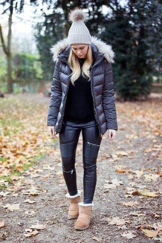 Cómo combinar: plumífero en gris oscuro, jersey con cuello circular negro, vaqueros pitillo de cuero negros, botas ugg en beige