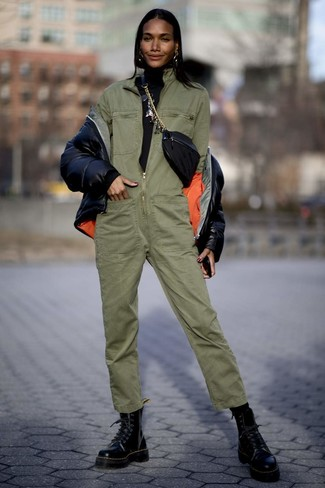 Cómo combinar: plumífero negro, jersey de cuello alto negro, mono verde oliva, botas planas con cordones de cuero negras