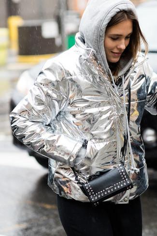 Cómo combinar: plumífero plateado, sudadera con capucha gris, vaqueros negros, cartera sobre de cuero con tachuelas negra