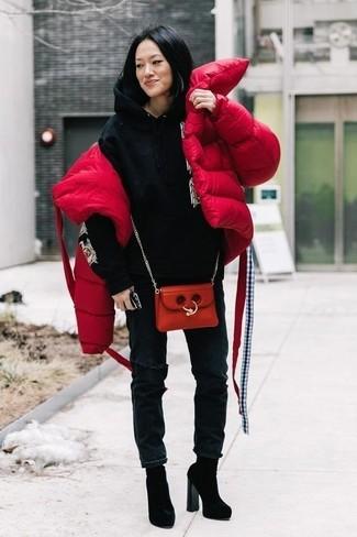 Cómo combinar: plumífero rojo, sudadera con capucha estampada negra, vaqueros desgastados negros, botines de ante negros