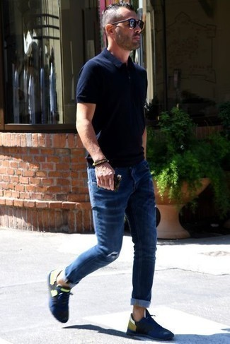 Men's Outfits 2021: A navy polo and navy ripped jeans make for the ultimate casual style for today's man. A pair of navy athletic shoes serves as the glue that will bring this look together.