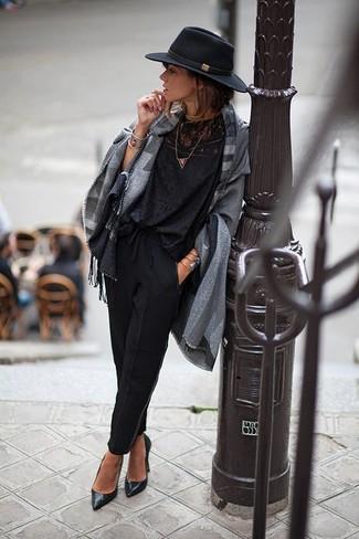 Cómo combinar: poncho de tartán gris, blusa de manga larga de encaje negra, pantalón de pinzas negro, zapatos de tacón de cuero negros
