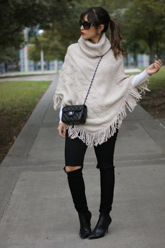 Pair a beige knit poncho with black ripped skinny jeans for an effortless kind of elegance. Dial up the cool of this look with a pair of black suede ankle boots.
