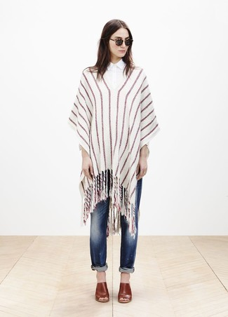 A beige vertical striped poncho and navy ripped boyfriend jeans are a go-to off-duty combination for many stylish women. Tone down the casualness of this ensemble by wearing a pair of tobacco leather mules.