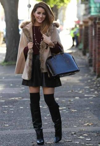 Cómo combinar: poncho en beige, jersey con cuello circular burdeos, falda skater de cuero negra, botas de caña alta de cuero negras