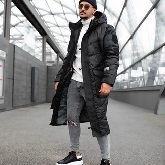 Black Puffer Coat Outfits For Men: Team a black puffer coat with grey ripped skinny jeans for an easy-to-create outfit. If you want to immediately rev up your ensemble with a pair of shoes, complement this getup with a pair of black and white leather low top sneakers.