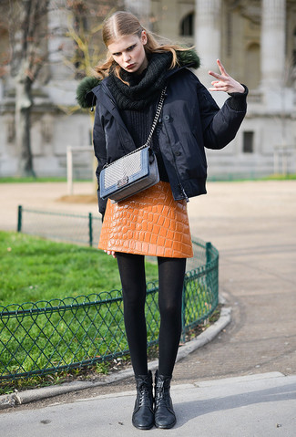 How to wear: black puffer jacket, black cowl-neck sweater, orange leather mini skirt, black leather lace-up flat boots