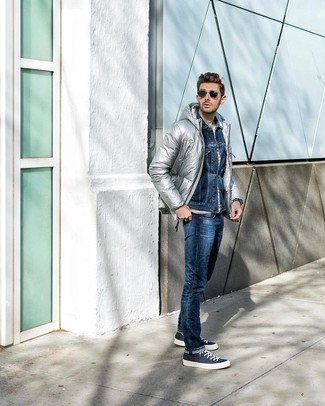 How to wear: silver puffer jacket, navy denim jacket, white horizontal striped crew-neck t-shirt, navy jeans