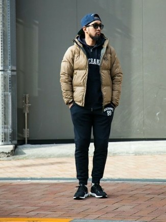 How to wear: tan puffer jacket, black and white print hoodie, black crew-neck t-shirt, black sweatpants