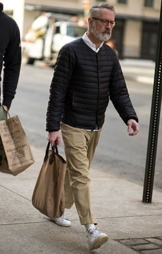 How to Wear Khaki Chinos: This pairing of a black puffer jacket and khaki chinos is a must-try classic and casual outfit for any gent. Want to break out of the mold? Then why not introduce white leather low top sneakers to your getup?