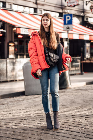 How to wear: red puffer jacket, black sweatshirt, blue skinny jeans, dark brown suede ankle boots