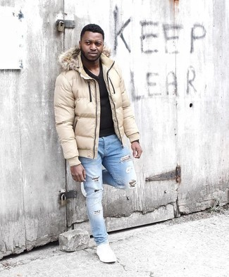 Puffer Jacket Outfits For Men: This pairing of a puffer jacket and light blue ripped skinny jeans will prove your expertise in men's fashion even on weekend days. White canvas low top sneakers will give an added dose of polish to an otherwise straightforward ensemble.
