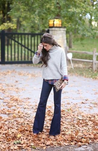 Essaie d'harmoniser un pull à col roulé en tricot gris avec un bracelet doré pour une tenue confortable aussi composée avec goût.