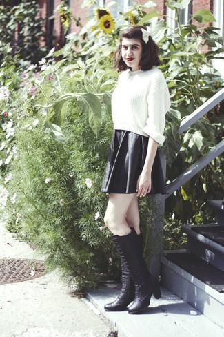 Marie un pull court en tricot blanc avec une jupe patineuse en cuir noire pour créer un look génial et idéal le week-end. Apportez une touche d'élégance à votre tenue avec une paire de des bottes hauteur genou en cuir noires.