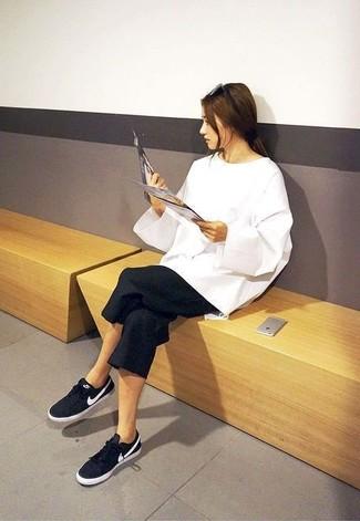 Pense à associer un pull surdimensionné blanc avec une jupe-culotte noire pour un look confortable et décontracté. Cette tenue se complète parfaitement avec une paire de des baskets basses noires.