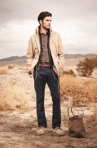 500+ Chill Weather Outfits For Men: This combo of a tan raincoat and charcoal chinos is put together and yet it's laid-back enough and ready for anything. When not sure as to what to wear when it comes to footwear, introduce a pair of beige suede desert boots to the equation.
