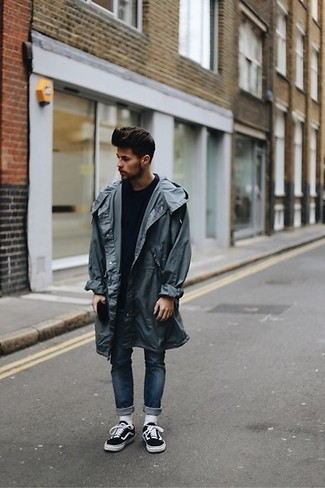 How to wear: charcoal raincoat, navy crew-neck sweater, navy skinny jeans, black and white canvas low top sneakers
