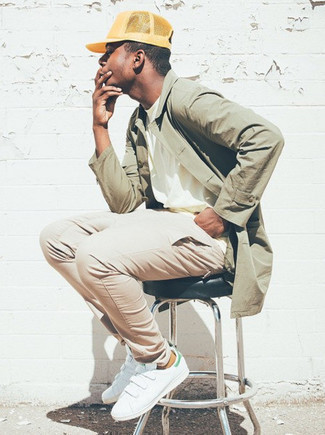 White and Green Leather Low Top Sneakers Outfits For Men: Such pieces as an olive raincoat and beige chinos are an easy way to introduce effortless cool into your daily styling arsenal. Introduce white and green leather low top sneakers to the equation and ta-da: this outfit is complete.