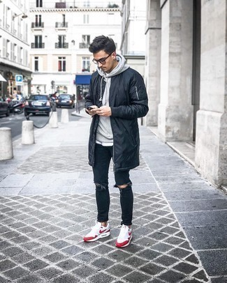 Grey Hoodie Outfits For Men: A grey hoodie and black ripped skinny jeans are a life-saving off-duty pairing for many sartorially savvy men. A pair of white and red athletic shoes makes your outfit whole.