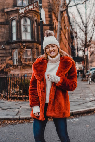 How to wear: red fur jacket, beige knit turtleneck, navy skinny jeans, white knit beanie