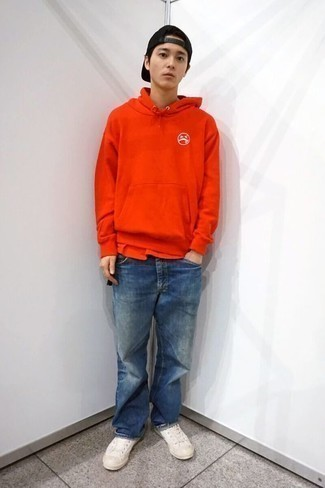 How to Wear Low Top Sneakers For Men: Marry a red hoodie with blue jeans for knockout menswear style. This ensemble is finished off nicely with low top sneakers.