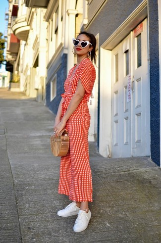 How to wear: red polka dot jumpsuit, white leather low top sneakers, tan straw clutch, black and white sunglasses
