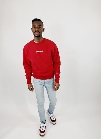White and Red Leather Low Top Sneakers Spring Outfits For Men: A red print sweatshirt and light blue jeans are indispensable menswear must-haves if you're figuring out a casual wardrobe that holds to the highest style standards. All you need now is a pair of white and red leather low top sneakers to round off this ensemble. Keep this combination in your front hall wardrobe when spring arrives, and we guarantee you'll save time crafting an outfit on more than one morning.
