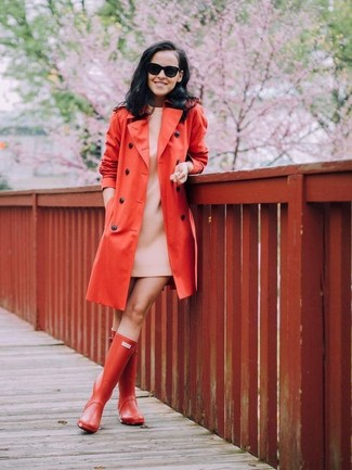 For an ensemble that's nothing less than drool-worthy, try teaming a red trenchcoat with a beige shift dress. To bring out the fun side of you, complete your getup with rain boots. You can be certain this look is great for fluctuating autumn weather.