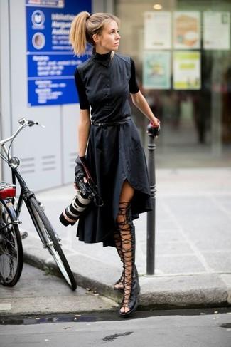 Harmonise une robe chemise noire avec des gants en cuir noirs pour obtenir un look relax mais stylé. Décoince cette tenue avec une paire de des sandales spartiates hautes en cuir noires.