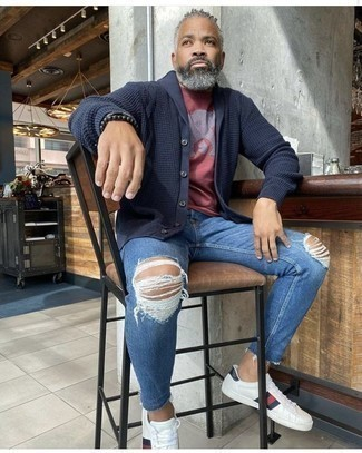 How to Wear White Print Leather Low Top Sneakers For Men: Stylish yet comfortable, this getup is assembled from a navy shawl cardigan and blue jeans. A nice pair of white print leather low top sneakers is an effortless way to upgrade this getup.