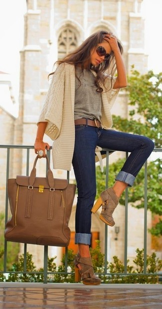 A beige shawl cardigan and navy slim jeans is a wonderful combination to carry you throughout the day. Make brown cutout suede ankle boots your footwear choice to instantly up the chic factor of any outfit. This one is is a great pick if you're picking out a standout getup for transitional weather.