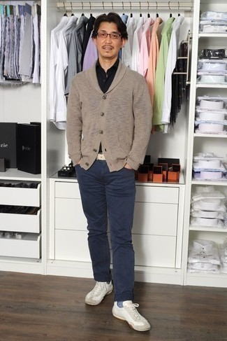 White Leather Low Top Sneakers Outfits For Men: Marrying a tan shawl cardigan with navy jeans is an on-point option for a relaxed casual outfit. White leather low top sneakers will bring a carefree vibe to an otherwise all-too-safe ensemble.
