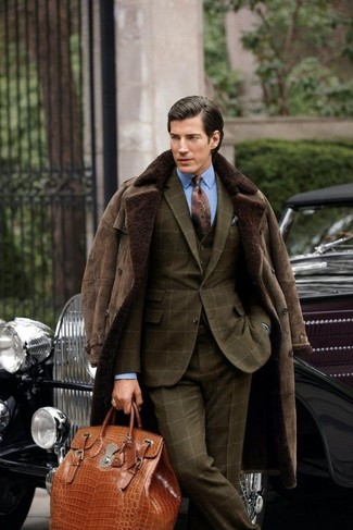 How to wear: dark brown shearling coat, olive check three piece suit, light blue dress shirt, tobacco leather holdall