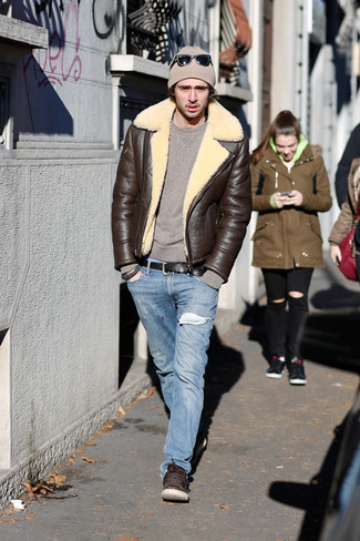 How to wear: dark brown shearling jacket, brown crew-neck sweater, light blue jeans, dark brown leather low top sneakers