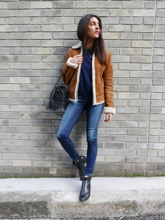 How to wear: tobacco shearling jacket, navy crew-neck sweater, blue skinny jeans, black leather ankle boots