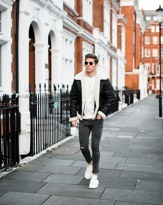 Charcoal Ripped Skinny Jeans Outfits For Men: A pulled together casual combination of a black and white shearling jacket and charcoal ripped skinny jeans will set you apart in an instant. A pair of white and black leather low top sneakers immediately kicks up the classy factor of this getup.