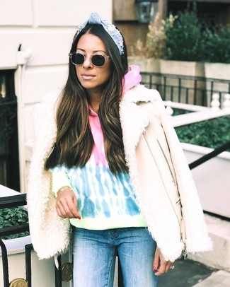 How to wear: beige shearling jacket, multi colored tie-dye hoodie, blue skinny jeans, black sunglasses