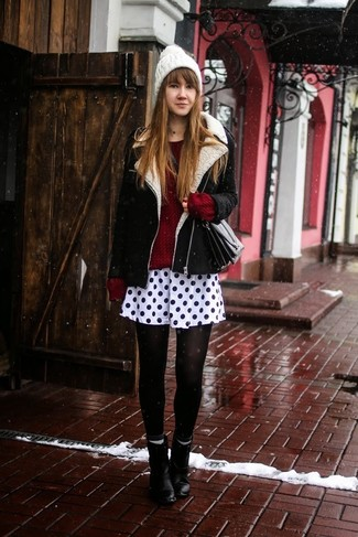 Wear a black and white shearling jacket with a monochrome polka dot pleated skirt for a comfortable outfit that's also put together nicely. Black leather ankle boots will bring a classic aesthetic to the ensemble.
