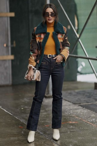 How to wear: multi colored shearling jacket, mustard turtleneck, navy flare jeans, white leather ankle boots