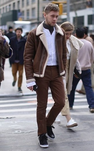 How to Wear a Brown Shearling Jacket For Men: A brown shearling jacket and brown chinos are a pairing that every smart man should have in his casual sartorial collection. Want to play it down in the shoe department? Complement your outfit with a pair of black leather low top sneakers for the day.