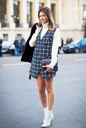 How to wear: black shearling jacket, beige turtleneck, navy check overall dress, white cutout leather ankle boots