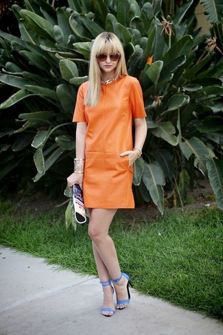 Opt for an orange leather shift dress for a work-approved look. Blue leather heeled sandals are a great choice to complete the look.