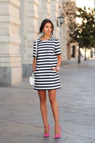 Make a white and black horizontal striped shift dress your outfit choice to feel confidently and look fashionably. Hot pink suede pumps are a savvy choice to complete the look.