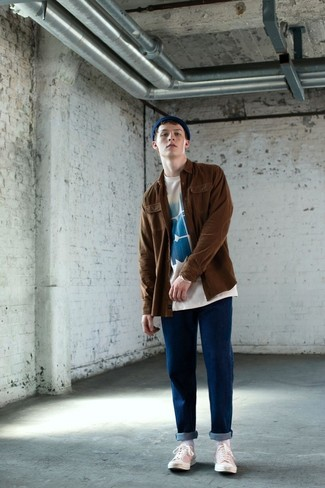 How to wear: brown shirt jacket, white and blue print crew-neck t-shirt, blue jeans, white canvas low top sneakers