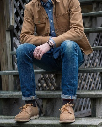 Blue Jeans Outfits For Men: A tan shirt jacket and blue jeans worn together are a perfect match. Tan suede derby shoes are the most effective way to inject an air of class into your getup.