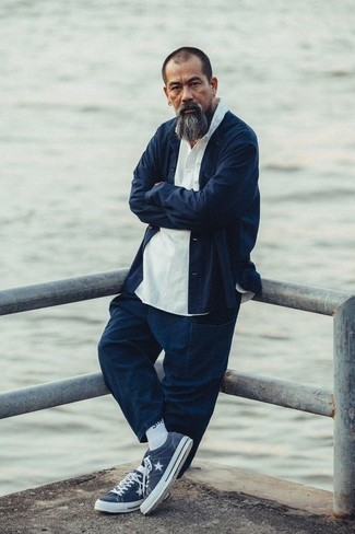 How to Wear Navy Chinos After 40: If you take your style seriously, go for a casually stylish ensemble in a navy shirt jacket and navy chinos. A pair of navy and white canvas low top sneakers will instantly dial down a classic look.